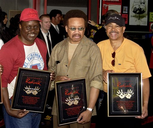 FILE - In this July 7, 2003 file photo, Philip Bailey, from left, Maurice White, and Ralph Johnson, of Earth Wind & Fire hold up the plaques from their induction at the Hollywood Rock Walk at a ceremony in Los Angeles. White, the founder and leader of Earth, Wind & Fire, died at home in Los Angeles, Wednesday, Feb. 3, 2016, said his brother, Verdine White. He was 74. (AP Photo/Matt Sayles, File)