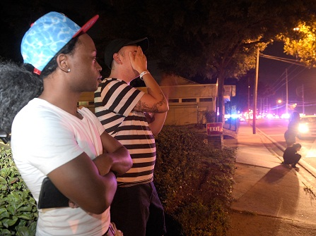 Jermaine Towns, left, and Brandon Shuford wait down the street from a multiple shooting at a nightclub in Orlando, Fla., Sunday, June 12, 2016. Towns said his brother was in the club at the time. A gunman opened fire at a nightclub in central Florida, and multiple people have been wounded, police said Sunday. (AP Photo/Phelan M. Ebenhack)