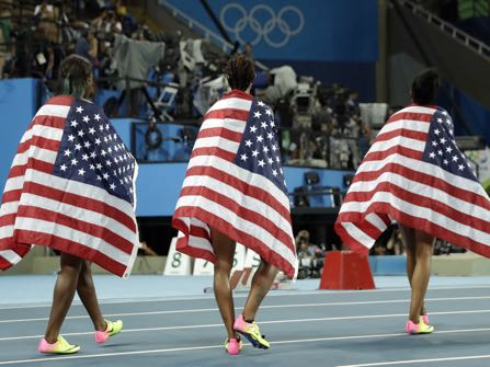 Gold medal winner Brianna Rollins, center, silver medal winner, Nia Ali, left , and bronze medal winner Kristi Castlin, all from the United States, pose with their country's flag after the 100-meter hurdles final, during the athletics competitions of the 2016 Summer Olympics at the Olympic stadium in Rio de Janeiro, Brazil, Wednesday, Aug. 17, 2016. (AP Photo/Matt Dunham)