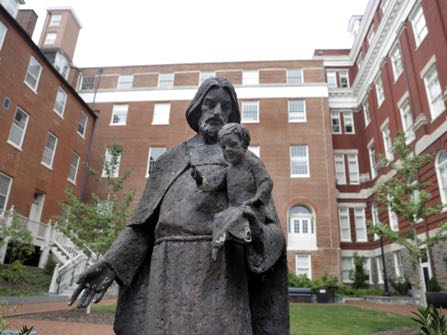 A Jesuit statue is seen in front of Freedom Hall, formerly named Mulledy Hall, on the Georgetown University campus, Thursday, Sept. 1, 2016, in Washington. After renaming the Mulledy and McSherry buildings at Georgetown University temporarily to Freedom Hall and Remembrance Hall, Georgetown University will give preference in admissions to the descendants of slaves owned by the Maryland Jesuits as part of its effort to atone for profiting from the sale of enslaved people. Georgetown president John DeGioia announced Thursday that the university will implement the admissions preferences. The university released a report calling on its leaders to offer a formal apology for the university's participation in the slave trade. (AP Photo/Jacquelyn Martin)