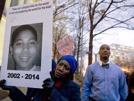 FILE - In a Monday, Dec. 1, 2014 file photo, Tomiko Shine holds up a picture of Tamir Rice, the 12 year old boy fatally shot on Nov. 22 by a rookie police officer, in Cleveland, Ohio, during a protest in response to a grand jury's decision in Ferguson, Mo. to not indict police officer Darren Wilson in the shooting death of Michael Brown, in Washington. For centuries, grand juries have held some of the criminal justice system's best-kept secrets. But their private process has come under extraordinary public scrutiny after high-profile decisions not to indict police officers in the deaths of unarmed men. Calls for more transparency have sounded in Congress, statehouses and editorial pages, mixed with notes of caution about forswearing secrecy that can safeguard witnesses and the accused. (AP Photo/Jose Luis Magana, File) (AP Photo/Jose Luis Magana))