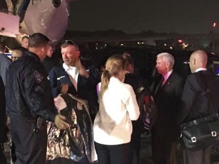 Republican vice presidential candidate Indiana Gov. Mike Pence, second from right, talks on the tarmac at New York's LaGuardia Airport after his campaign plane slide, back left, off the runway while landing on Thursday, Oct. 27, 2016. (AP Photo/Will Weissert)
