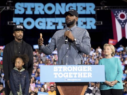 LeBron James, center, accompanied by Cleveland Cavaliers basketball player J. R. Smith, left, his daughter Demi, bottom left, and Democratic presidential candidate Hillary Clinton, right, speaks at a rally at the Cleveland Public Auditorium in Cleveland, Sunday, Nov. 6, 2016. (AP Photo/Andrew Harnik)