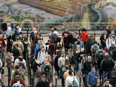 Travellers queue up at a security checkpoint with a mural in the background at Denver International Airport early Wednesday, Nov. 23, 2016, in Denver. Travellers are criss-crossing the country Wednesday, clogging airport terminals in a rush to reach their Thanksgiving Day destinations. (AP Photo/David Zalubowski)