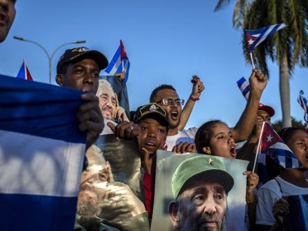 People hold pictures of late Fidel Castro near Santa Ifigenia cemetery in Santiago, Cuba, Sunday, Dec. 4, 2016. Thousands of people lined the short route from the Plaza Antonio Maceo or Plaza of the Revolution to the cemetery where the ashes were be buried in a private ceremony near the grave of Cuba's independence hero Jose Marti. (AP Photo/Desmond Boylan)