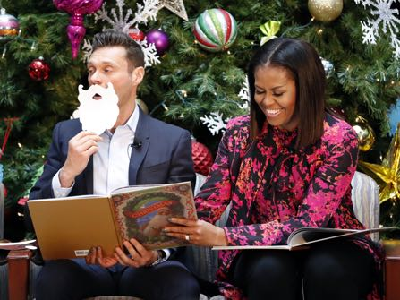 """First lady Michelle Obama, right, with television and radio host Ryan Seacrest, read """"Twas the Night Before Christmas,"""" during a holiday event at Children's National Health System on Monday, Dec. 12, 2016 in Washington. Obama toured the facility, visited with patients and families, read """"Twas the Night Before Christmas"""" to children and participated in a broadcast with Seacrest. (AP Photo/Alex Brandon)"""