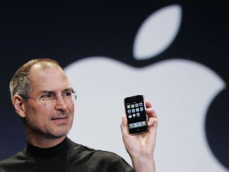 """FILE- In this Jan. 9, 2007, file photo, Apple CEO Steve Jobs holds up an iPhone at the MacWorld Conference in San Francisco. Jobs introduced the first iPhone a decade ago. Jobs' """"magical product"""" reshaped culture, shook up industries and made it seem possible to do just about anything with a few taps on a screen while walking around with the equivalent of a computer in our pocket. (AP Photo/Paul Sakuma, File)"""