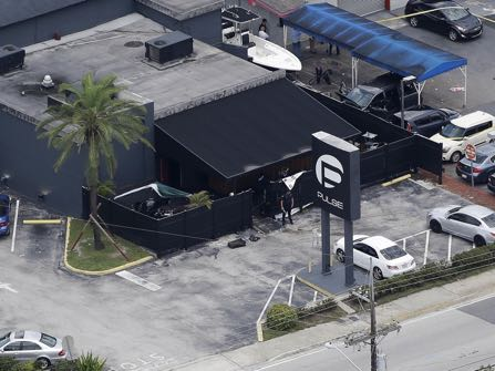 Law enforcement officials work at the Pulse Orlando nightclub following a fatal shooting Sunday, June 12, 2016, in Orlando, Fla. . (AP Photo/Chris O'Meara)